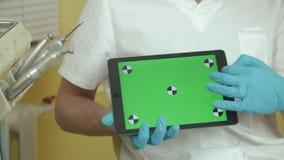 De tandarts houdt een tablet met het groen scherm voor uw inhoud stock videobeelden