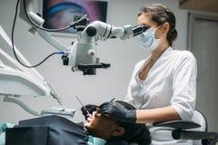 De tandarts maakt tot chirurgie aan vrouw, tandkliniek stock fotografie