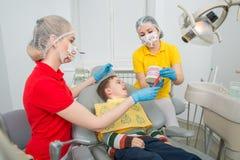 De tandarts met hulp tonend de kleine jongen hoe te om de tanden met een tandenborstel op een kunstmatig kaakmodel schoon te make stock foto