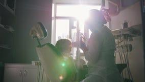 De tandarts onderzoekt en leidt de procedure om kleine meisjes` s tanden te borstelen stock videobeelden