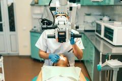 De tandarts onderzoekt mondholte van vrouwelijke patiënt met microscoop stock foto