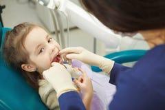 De tandarts in rubberhandschoenen controleert mond van kind royalty-vrije stock fotografie