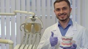 De tandarts toont de lay-out van menselijke tanden aan stock videobeelden