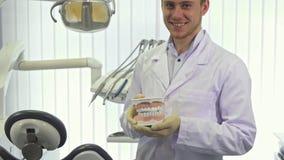 De tandarts toont lay-out van menselijke tanden op het kantoor stock videobeelden