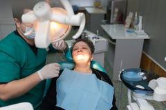 De tandarts werkt met de cliënt in de kliniek royalty-vrije stock afbeelding