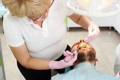 De tandartsvrouw maakt verdovende injectie binnen de geduldige mond van ` s stock foto's