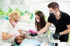 De tandartswerken met patiënt, wordt zij bijgestaan door twee medewerkers stock foto's
