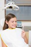 De tandenborstel van de meisjeholding als tandartsenvoorzitter Royalty-vrije Stock Afbeeldingen