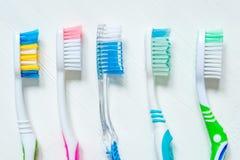 De tandenborstels van verschillende kleuren sluiten omhoog op een witte uitstekende achtergrond Mening van hierboven royalty-vrije stock foto
