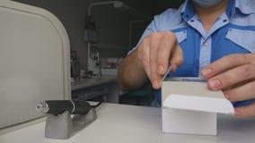 De tandtechnicus in een tandlaboratorium opent de doos met was stock videobeelden
