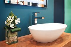 De tapkraanmixer van de luxe moderne stijl op een witte ronde gootsteen in mooie donkerblauwe badkamers Stock Foto