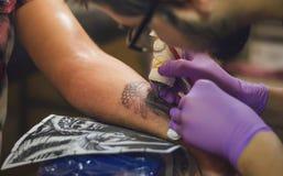 De tatoegeringskunstenaar doet de tatoegering op zijn wapen Royalty-vrije Stock Foto's