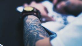 De tatoegeringskunstenaar maakt een schets op papier stock footage