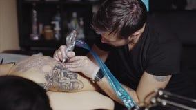 De tatoegeringskunstenaar maakt tatoegering bij de studio stock footage
