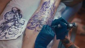 De tatoegeringskunstenaar maakt tatoegering bij de studio Te voet het tatoeëren stock footage