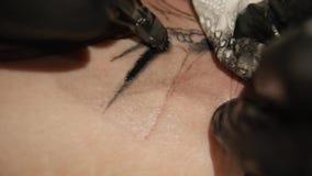 De tatoegeringskunstenaar maakt tatoegering in studio, tatoeërend op het lichaam Sluit omhoog stock videobeelden