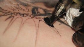 De tatoegeringskunstenaar maakt tatoegering in studio, tatoeërend op het lichaam Sluit omhoog stock footage