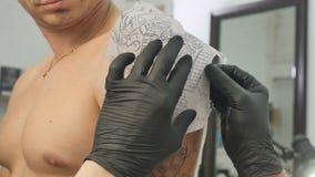 De tatoegeringskunstenaar past de schets op de mensen` s hand toe stock video