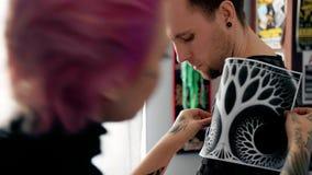 De tatoegeringskunstenaar probeert op een schets op de cliënt` s schouder stock footage