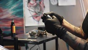 De tatoegeringskunstenaar verzamelt de tatoegeringsmachine de meester van de meisjestatoegering bereidt een roterend tatoegerings stock videobeelden