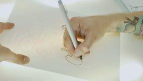 De tatoegeringskunstenaar zet het trekken op het vindende document op het glas met licht stock videobeelden