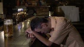 De te dronken kerel die zijn hoofd op de bar houden kan niet zijn glas bereiken - stock footage