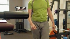 De te zware man doet hurkzit met hurkzit met een gewichtsschijf voor een barbell De mens van de geschiktheid training Gezond leve stock videobeelden