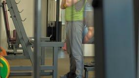 De te zware man doet hurkzit met hurkzit met een gewichtsschijf voor een barbell De mens van de geschiktheid training Gezond leve stock video