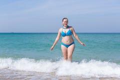 De te zware midden oude vrouw komt uit zeewater royalty-vrije stock afbeelding