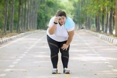 De te zware vrouw kijkt vermoeid na jogging stock fotografie
