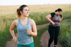 De te zware vrouw neemt adem bij joggingtraining stock afbeeldingen