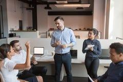 De teamleider bespreekt het werkkwesties met collega's bij informele briefing royalty-vrije stock afbeeldingen