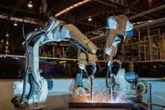 De teamrobots lassen assemblagedeel in autofabriek stock afbeelding