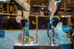 De teamrobots lassen deel in industriële fabriek stock fotografie