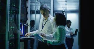 De technici werken aan laptop in een datacentrum stock footage