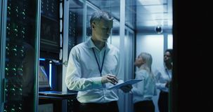 De technici werken aan laptop in een datacentrum stock video