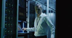 De technici werken aan laptop in een datacentrum stock videobeelden