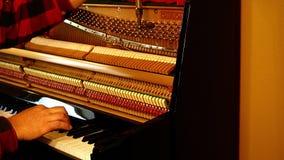 De technicus die een pianino stemmen door zwart-witte sleutels te spelen en te gebruiken tilt en hulpmiddelen op om de koorden aa stock footage