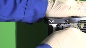 De technicus dient handschoenen in stopt in elektrische kabel aan PC en drukknop stock footage