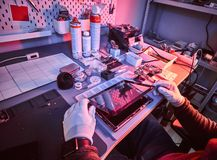 De technicus herstelt een gebroken tabletcomputer in een reparatiewerkplaats Verlichting met rode en blauwe lichten royalty-vrije stock foto