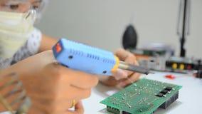 De technicus soldeert aan de elektronische raad van de drukkring stock footage