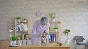 De technicus van het vrouwenlaboratorium leidt onderzoek gebruikend een microscoop stock video