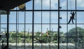 De technicus van de kabeltoegang wast binnen een muur van het hotel complexe glas van Stock Fotografie
