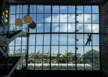De technicus van de kabeltoegang wast binnen een muur van het hotel complexe glas van Royalty-vrije Stock Afbeelding