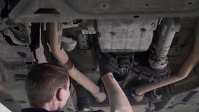 De technicus voert diagnostiek en reparatie onder lichaamsauto uit stock video