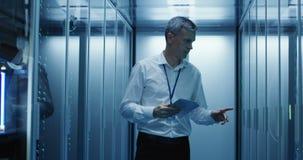 De technicuswerken aangaande een tablet in een datacentrum stock video