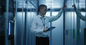 De technicuswerken aangaande een tablet in een datacentrum stock footage