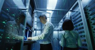 De technicuswerken aangaande laptop in een datacentrum stock video