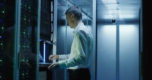 De technicuswerken aangaande laptop in een datacentrum stock footage