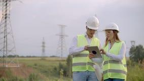 De techniek die aan toren Met hoog voltage werken, controleert de informatie over tabletcomputer twee werknemersman en vrouw stock videobeelden